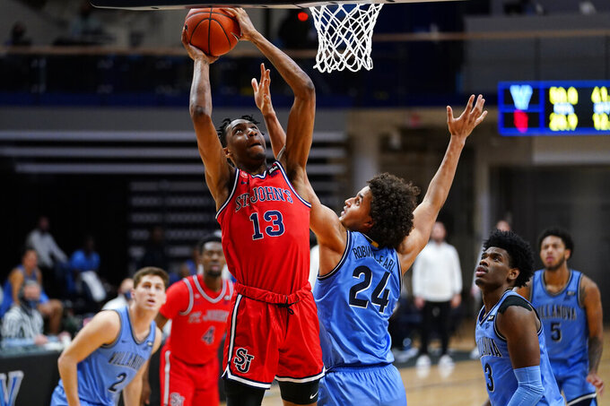 St. John's Isaih Moore (13) goes up for a shot against Villanova's Jeremiah Robinson-Earl (24) during the second half of an NCAA college basketball game, Tuesday, Feb. 23, 2021, in Villanova, Pa. (AP Photo/Matt Slocum)