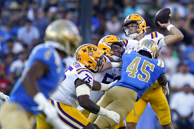 LSU quarterback Max Johnson, right, throws under pressure from UCLA linebacker Mitchell Agude (45) during the first half of an NCAA college football game Saturday, Sept. 4, 2021, in Pasadena, Calif. (AP Photo/Marcio Jose Sanchez)
