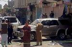Police officers and local residents gather beside damaged vehicles at the site of a bomb blast in Chaman, the southwestern Pakistan, Friday, May 21, 2021. A powerful roadside bomb went off near a vehicle carrying a local leader of an Islamist political party in Pakistan's southwestern border town of Chaman on Friday, killing multiple people and wounding several others, police and a government spokesman said. (AP Photo/Jan Achakzai)