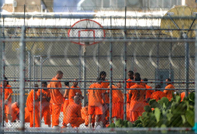 FILE - In this July 4, 2015, file photo, prison inmates stand in the yard at Arizona State Prison-Kingman in Golden Valley, Ariz. A book that discusses the impact of the criminal justice system on black men is being kept out of the hands of Arizona prison inmates. The American Civil Liberties Union is calling on the Arizona Department of Corrections to rescind a ban on