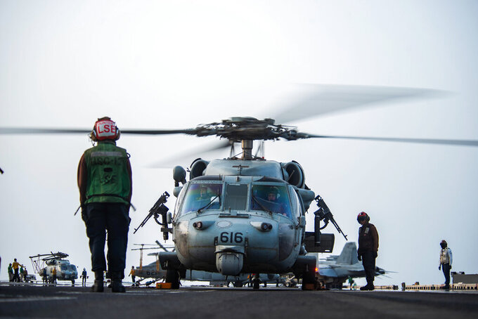 In this photo provided by the U.S. Navy, sailors on board an MH-60S Seahawk helicopter on the flight deck of aircraft carrier USS Ronald Reagan prepare to head to an oil tanker that was attacked off the coast of Oman in the Arabian Sea on Friday, July 30, 2021. An attack on an oil tanker linked to an Israeli billionaire killed two crew members off Oman in the Arabian Sea, authorities said Friday, marking the first fatalities after years of assaults targeting shipping in the region. (Mass Communication Specialist 2nd Class Quinton A. Lee/U.S. Navy, via AP)