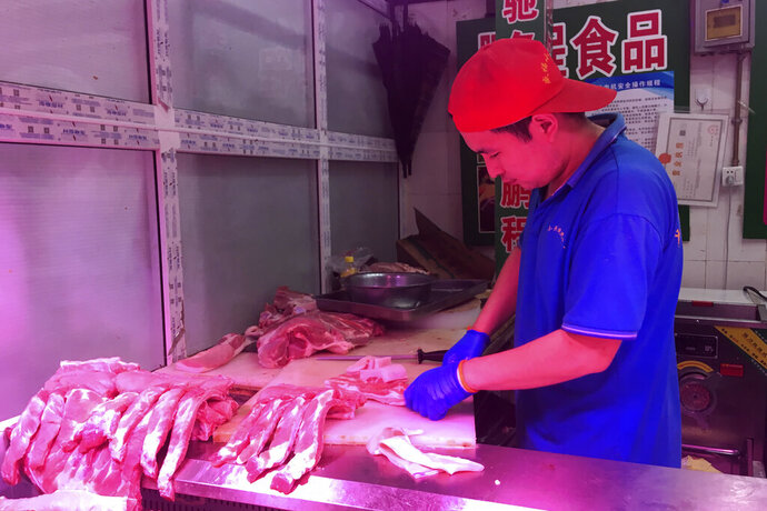 In this Wednesday, Sept. 11, 2019, photo, a butcher slices cuts of pork at a meat market in Beijing. China's government said Wednesday, Sept. 18, 2019, that is releasing pork from official stockpiles to ease a shortage and cool surging prices ahead of Oct. 1 celebrations of the Communist Party's 70th anniversary in power. (AP Photo/Fu Ting)