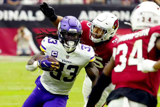 Minnesota Vikings running back Dalvin Cook (33) avoids the tackles of Arizona Cardinals linebacker Zaven Collins during the first half of an NFL football game, Sunday, Sept. 19, 2021, in Glendale, Ariz. (AP Photo/Rick Scuteri)