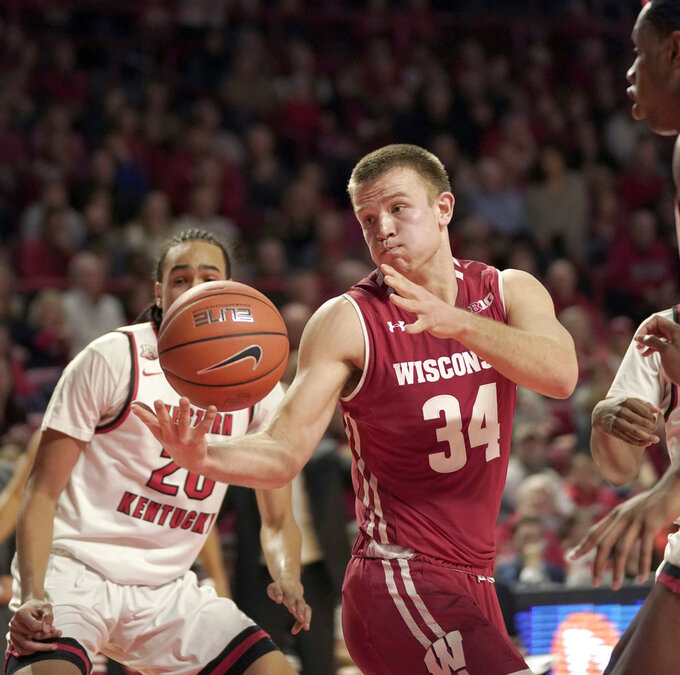 Wisconsin guard Brad Davison (34) tries to hold on to the ball as Western Kentucky guard Dalano Banton (20) defends during the first half of an NCAA college basketball game Saturday, Dec. 29, 2018, in Bowling Green, Ky. (AP Photo/Tim Broekema)