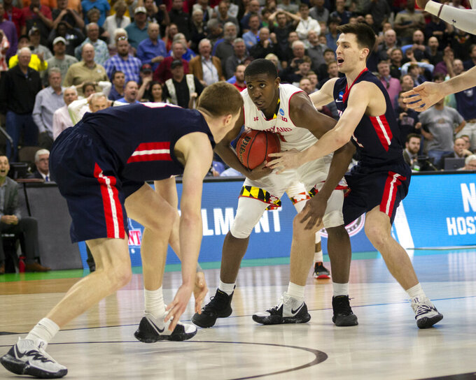Maryland guard Darryl Morsell, center, hangs onto an intercepted pass between Belmont 's Dylan Windler, left, as he is fouled by Belmont's Grayson Murphy, right, during the final moments of the first round men's college basketball game in the NCAA Tournament in Jacksonville, Fla., Thursday, March 21, 2019. (AP Photo/Stephen B. Morton)