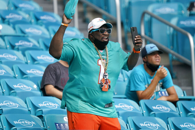 A Miami Dolphins fan cheers after the team scores a touchdown, during the first half of an NFL football game against the Buffalo Bills, Sunday, Sept. 20, 2020 in Miami Gardens, Fla. (AP Photo/Wilfredo Lee)