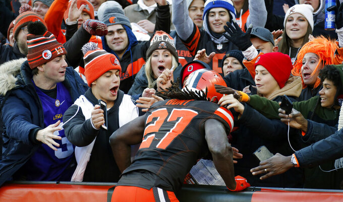 Cleveland Browns fans celebrate with Kareem Hunt (27) after he scored a 6-yard touchdown during the first half of an NFL football game against the Miami Dolphins, Sunday, Nov. 24, 2019, in Cleveland. (AP Photo/Ron Schwane)