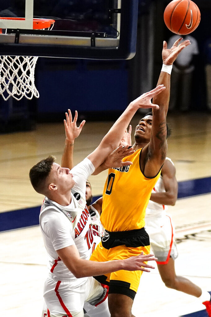 Grambling guard Cameron Woodall is fouled by Arizona forward Azuolas Tubelis (10) during the first half of an NCAA college basketball game Friday, Nov. 27, 2020, in Tucson, Ariz. (AP Photo/Rick Scuteri)