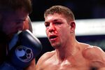 Vincent Feigenbutz, of Germany, shows a bloody nose as he fights Caleb Plant, left, during the IBF super middleweight championship boxing match Saturday, Feb. 15, 2020, in Nashville, Tenn. (AP Photo/Mark Humphrey)