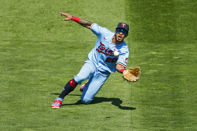 FILE - In this Aug. 16, 2020, file photo, Minnesota Twins left fielder Eddie Rosario slides to make a catch of a ball hit by Kansas City Royals' Hunter Dozier during the sixth inning of a baseball game in Minneapolis. The Indians have agreed with free agent outfielder Rosario on a contract, a person familiar with the negotiations told the Associated Press on Friday night, Jan. 29, 2021. Rosario's deal is pending the completion of a physical, said the person who spoke on condition of anonymity because the medical tests aren't finished. (AP Photo/Bruce Kluckhohn, File)