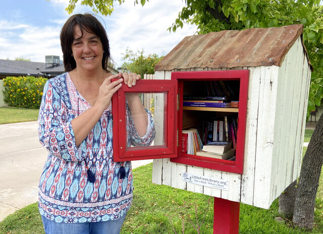 Kerri Kaplan, a fifth grade teacher, stands next to a small library she has in her front yard in Phoenix, Ariz., on Friday, April 17, 2020. As government orders shuttered public libraries to slow the spread of coronavirus, some have turned to official and unofficial book-sharing means to satisfy their desire for new reading material.  (AP Photo/Michelle A. Monroe)