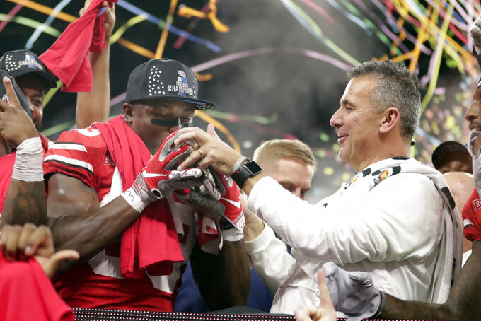 Ohio State's Terry McLaurin (83) kisses the trophy along side head coach Urban Meyer Sunday, Dec. 2, 2018, after defeating Northwestern in the Big Ten championship NCAA college football game, in Indianapolis. Ohio State won 45-24. (AP Photo/Michael Conroy)
