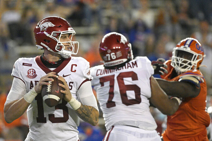 Arkansas quarterback Feleipe Franks (13) sets up to throw a pass as offensive lineman Myron Cunningham (76) blocks Florida defensive lineman Zachary Carter, right, during the first half of an NCAA college football game, Saturday, Nov. 14, 2020, in Gainesville, Fla. (AP Photo/Phelan M. Ebenhack)