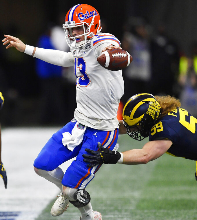 Florida quarterback Feleipe Franks (13) runs against Michigan linebacker Noah Furbush (59) during the first half of the Peach Bowl NCAA college football game, Saturday, Dec. 29, 2018, in Atlanta. (AP Photo/Mike Stewart)