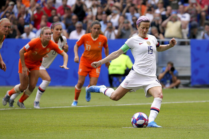 FILE - In this July 7, 2019, file photo, United States' Megan Rapinoe scores her side's opening goal from the penalty shot during the Women's World Cup final soccer match against The Netherlands at the Stade de Lyon in Decines, outside Lyon, France.  Rapinoe has returned to the U.S. national team after sitting out most of last year following the SheBelieves Cup tournament, joining the squad for its January training camp in Florida.  (AP Photo/David Vincent, File)