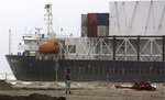A Pakistan Navy officer stands near the stranded Heng Tong 77 cargo ship at Sea View Beach near the southern port city of Karachi, Pakistan, Monday, July 26, 2021. Pakistani authorities said they are working on plans to refloat the cargo ship that ran aground last week amid bad weather en route to Istanbul from China. (AP Photo/Fareed Khan)