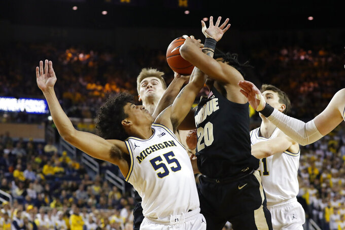 Michigan guard Eli Brooks (55) and Purdue guard Nojel Eastern (20) compete for a rebound during the first half of an NCAA college basketball game in Ann Arbor, Mich., Thursday, Jan. 9, 2020. (AP Photo/Paul Sancya)