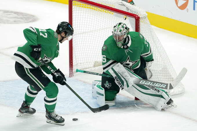Dallas Stars' Nick Caamano (17) helps clear the puck away from the net as goaltender Anton Khudobin watches during the first period of the team's NHL hockey game against the Nashville Predators in Dallas, Friday, Jan. 22, 2021. (AP Photo/Tony Gutierrez)