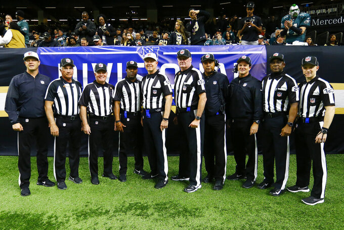 NFL officials from left to right, Craig Wrolstad, Perry Paganelli, Jeff Bergman, John Jenkins, Carl Cheffers, Ed Camp, Byron Boston, Jim Quirk, Barry Anderson, Jonah Monroe pose for a photo before an NFL divisional playoff football game in New Orleans, Sunday, Jan. 13, 2019. (AP Photo/Butch Dill)