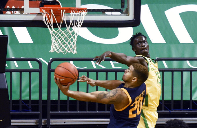 Oregon forward Lok Wur (15) defends against California guard Matt Bradley (20) during the second half of an NCAA college basketball game Thursday, Dec. 31, 2020, in Eugene, Ore. (AP Photo/Andy Nelson)