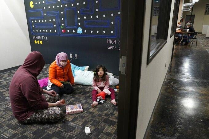 Christopher Harris, left, his wife Novi, center, and their daughter Keeva, occupy an office suite at a pop-up warming center in Richardson, Texas, Tuesday, Feb. 16, 2021. In cooperation with the cities emergency management center, this location is one of seven that have opened in the city, offering those in need a place to keep warm and have access to power supply to charge devices. This particular location is a 24-hour location whereas the six others will be open on Wednesday, and Thursday if needed for limited hours. (AP Photo/Tony Gutierrez)