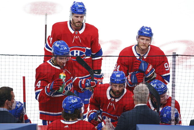 Montreal Canadiens' Nick Suzuki (14), Joel Edmundson (44), Corey Perry (94) and Tomas Tatar (90) listen to head coach Dominique Ducharme during a break in play during the third period of Game 4 of an NHL hockey Stanley Cup first-round playoff series against the Toronto Maple Leafs, Tuesday, May 25, 2021 in Montreal. (Paul Chiasson/The Canadian Press via AP)