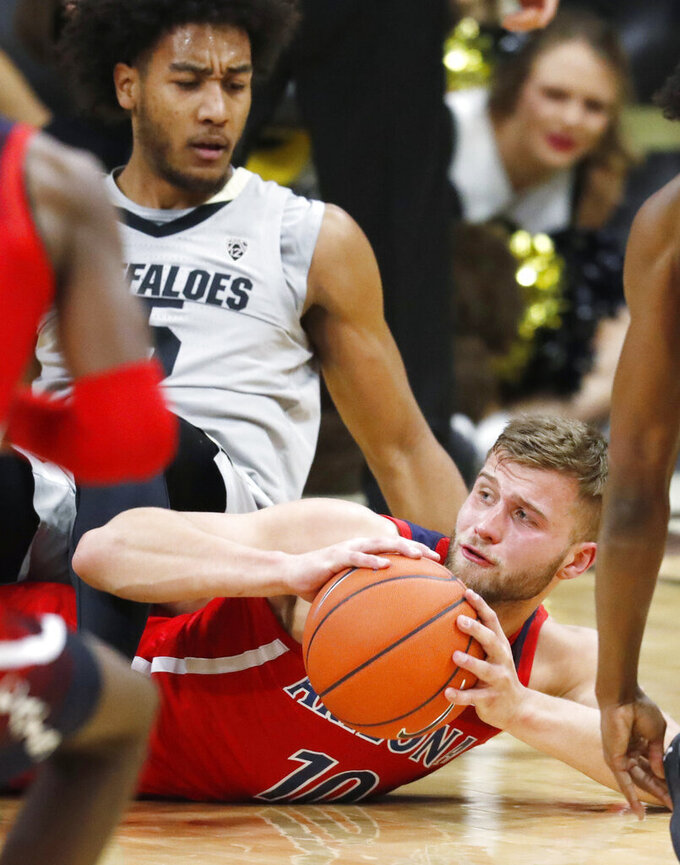 Arizona Wildcats forward Ryan Luther, bottom, recovers a loose ball as Colorado Buffaloes guard D'Shawn Schwartz tumbles on Luther in the first half of an NCAA college basketball game Sunday, Feb. 17, 2019, in Boulder, Colo. (AP Photo/David Zalubowski)