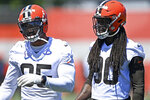 FILE - In this June 17, 2021, file photo, Cleveland Browns defensive linemen Jadeveon Clowney, right, and Myles Garrett watch during NFL football practice in Berea, Ohio. he Browns will have at least seven new starters on defense — maybe more depending on the package they're in — when the season kicks off Sunday against the Kansas City Chiefs at Arrowhead. (AP Photo/David Dermer, File)