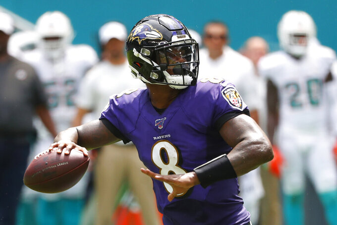 FILE - In this Sunday, Sept. 8, 2019, file photo, Baltimore Ravens quarterback Lamar Jackson (8) looks to pass during the first half at an NFL football game against the Miami Dolphins in Miami Gardens, Fla. Jackson, Heisman Trophy owner (2016), meets Kyler Murray, who took that award last season on Sunday when the Ravens host the Arizona Cardinals. (AP Photo/Wilfredo Lee, File)