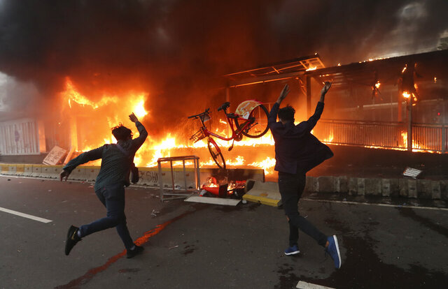 Protesters add a bicycle to a burning metro station during a rally in Jakarta, Indonesia, Thursday, Oct. 8, 2020. Thousands of enraged students and workers staged rallies across Indonesia on Thursday in opposition to a new law they say will cripple labor rights and harm the environment. (AP Photo/Achmad Ibrahim)