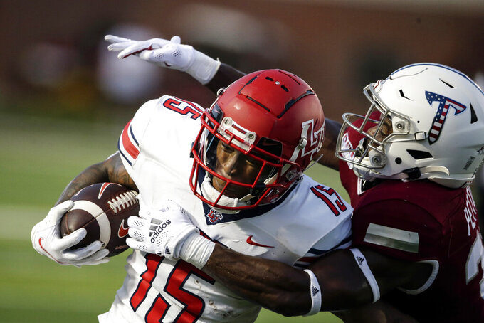Liberty running back T.J. Green (15) is tacked by Troy safety Dell Pettus, right, as he carries the ball during the first half of an NCAA college football game Saturday, Sept. 11, 2021, in Troy, Ala. (AP Photo/Butch Dill)