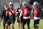 Las Vegas Raiders quarterback Derek Carr (4) looks to pass beside quarterback Marcus Mariota (8) and quarterback Nathan Peterman (3) during an NFL football practice Tuesday, June 15, 2021, in Henderson, Nev. (AP Photo/John Locher)