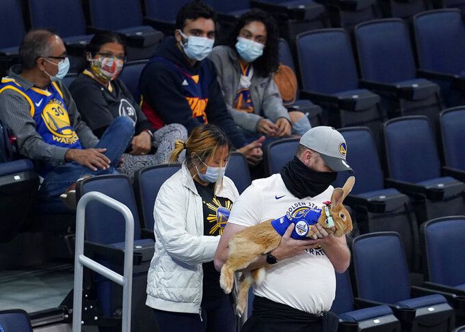 Josh Row, right, carries a therapy rabbit named Alex in front of his fiancee, Kei Kato, as they walk to their seats at Chase Center before an NBA basketball game between the Golden State Warriors and the Phoenix Suns in San Francisco, Tuesday, May 11, 2021. (AP Photo/Jeff Chiu)