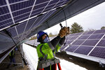 Electrician Zach Newton works on wiring solar panels at the 38-acre BNRG/Dirigo solar farm, Thursday, Jan. 14, 2021, in Oxford, Maine. President Joe Biden wants to change the way the U.S. uses energy by expanding renewables, but faces several challenges. (AP Photo/Robert F. Bukaty)