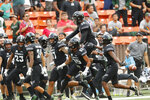 The Hawaii bench celebrates after Hawaii defensive back Kai Kaneshiro (24) intercepted an Arizona pass during the first quarter of an NCAA college football game Saturday, Aug. 24, 2019, in Honolulu. (AP Photo/Marco Garcia)