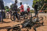 The burned motorcycle of an opposition activist, who was lightly injured and fled, lies on the ground as supporters of the ruling Rally of the Guinean People (RPG) party demonstrate against the opposition Union of Democratic Forces of Guinea (UFDG) party and to block the visit of their leader, in the streets of Kankan, Guinea Sunday, Oct. 11, 2020. The stage is set for Oct. 18 presidential elections pitting incumbent President Alpha Conde, 82, who is bidding for a third term, against opposition leader Cellou Dalein Diallo, who was previously defeated by Conde in both the 2010 and 2015 elections. (AP Photo/Sadak Souici)
