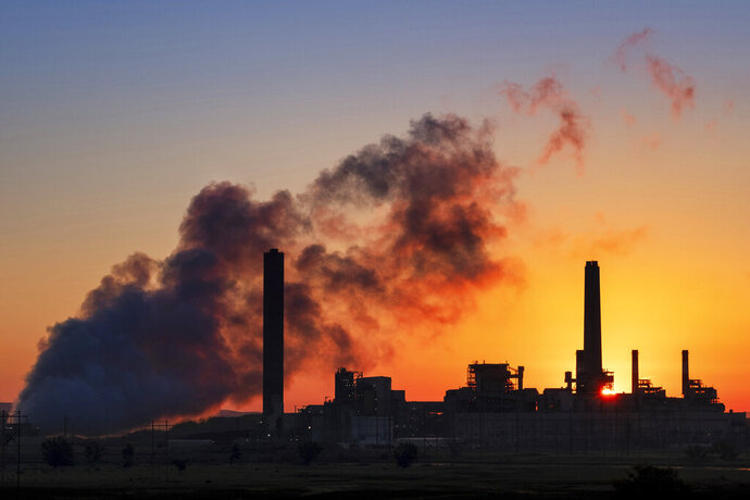 FILE - In this July 27, 2018 photo, the Dave Johnson coal-fired power plant is silhouetted against the morning sun in Glenrock, Wyo. The Trump administration is proposing easing more Obama-era protections on contaminants from coal-fired power plants. Environmental Protection Agency administrator Andrew Wheeler signed a proposal Monday overhauling a 2015 rule on release of contaminated wastewater from power plants.  The EPA says the change will save $175 million annually in compliance costs.(AP Photo/J. David Ake)
