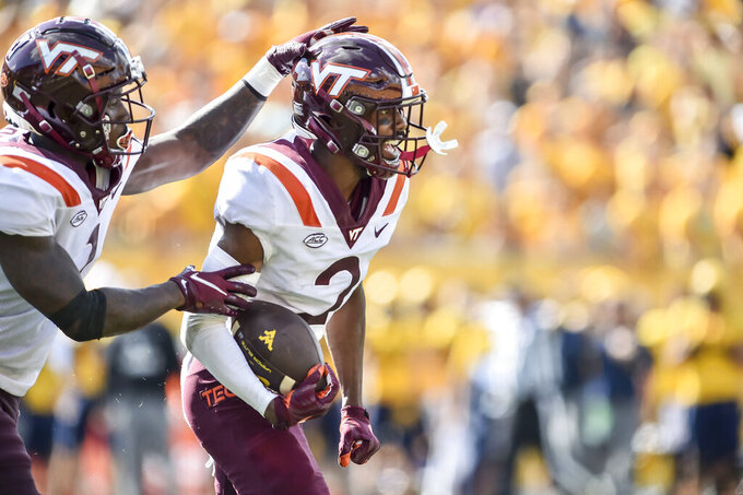 Virginia Tech defensive back Jermaine Waller (2) reacts after he makes an interception late in the second half of an NCAA college football game against West Virginia in Morgantown, W.Va., Saturday, Sep. 18, 2021. (AP Photo/William Wotring)