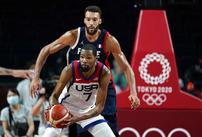 United States' Kevin Durant (7) drives around France's Rudy Gobert (27) during men's basketball gold medal game at the 2020 Summer Olympics, Saturday, Aug. 7, 2021, in Saitama, Japan. (AP Photo/Charlie Neibergall)