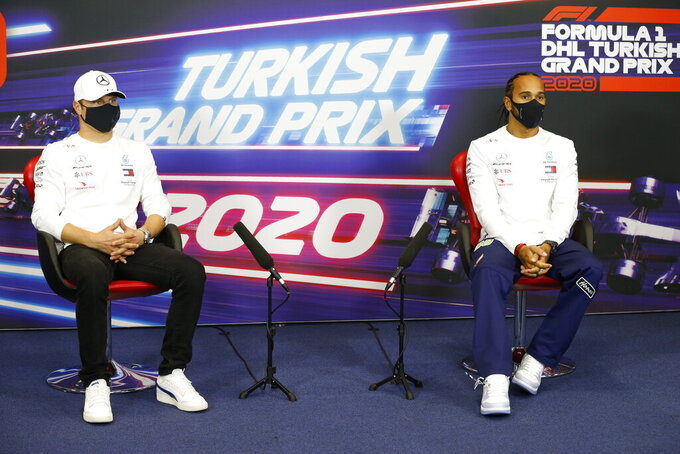 Mercedes drivers Valtteri Bottas of Finland, left and Lewis Hamilton of Britain attend a news conference at the Istanbul Park circuit racetrack in Istanbul, Thursday, Nov. 12, 2020, ahead of the Formula One Turkish Grand Prix that will take place on Sunday. (Antonin Vincent/Pool via AP)
