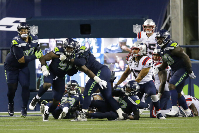 Seattle Seahawks players celebrate after they stopped New England Patriots quarterback Cam Newton near the goal line as the clock expired during the fourth quarter of an NFL football game, Sunday, Sept. 20, 2020, in Seattle. The Seahawks won 35-30. (AP Photo/John Froschauer)