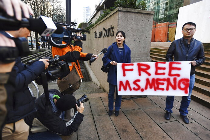 People hold a sign at a Vancouver, British Columbia courthouse prior to the bail hearing for Meng Wanzhou, Huawei's chief financial officer on Monday, December 10, 2018. Meng Wanzhou was detained at the request of the U.S. during a layover at the Vancouver airport on Dec. 1.(Jonathan Hayward/The Canadian Press via AP)