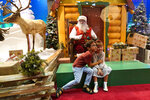 Theo and Sophy Morris, visiting from Hawaii with their family, pose for a photograph with Santa Claus, who is sitting behind a transparent barrier, at Bass Pro Shops, Friday, Nov. 20, 2020, in Miami. This is Santa Claus in the Coronavirus Age, where visits are done with layers of protection or moved online. Putting hundreds of kids a day onto your lap to talk directly into your face — that's not happening. (AP Photo/Lynne Sladky)