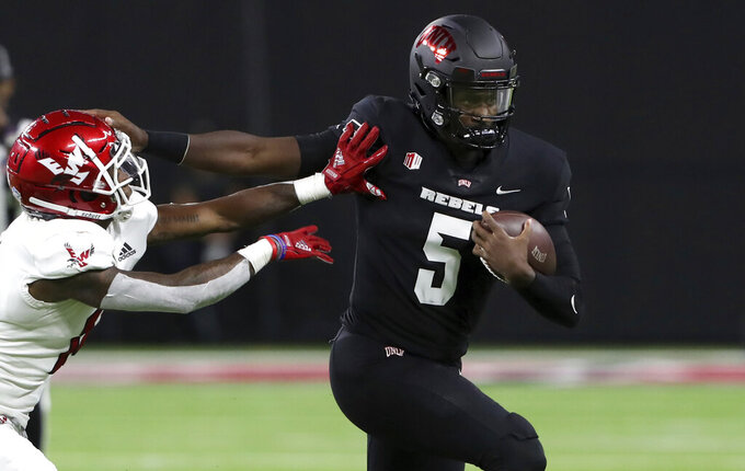 UNLV quarterback Justin Rogers (5) fends off a tackle attempt by Eastern Washington defensive back Darrien Sampson (14) during the first half of an NCAA college football game Thursday, Sept. 2, 2021, in Las Vegas. (Steve Marcus/Las Vegas Sun via AP)