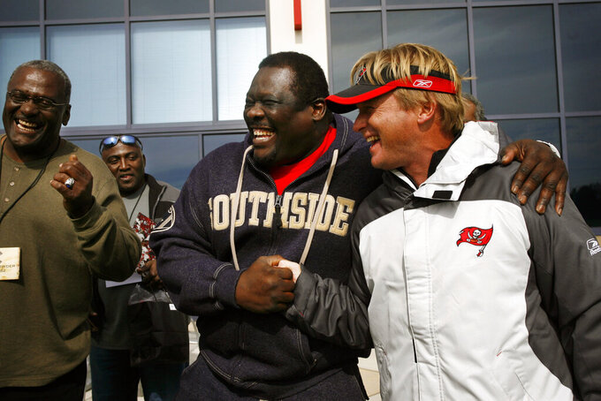 In this Dec. 8, 2006, photo, former Tampa Bay Buccaneers NFL football player David Lewis shakes hands while joking with Tampa Bay Buccaneers head coach Jon Gruden, right, after a Bucs practice in Tampa, Fla. Former Bucs nose tackle Randy Crowder is at far left. Former Bucs defensive player Johnny Ray Smith is at rear, second from left. Lewis, a key member of the Tampa Bay Buccaneers' 1979 team that reached the NFC title game, has died. He was 65. Lewis died Tuesday, July 14, 2020, in Tampa. The cause was not immediately known, but he had struggled with health issues in recent years, according to Southern California, where he played in college. (Carrie Pratt/Tampa Bay Times via AP)