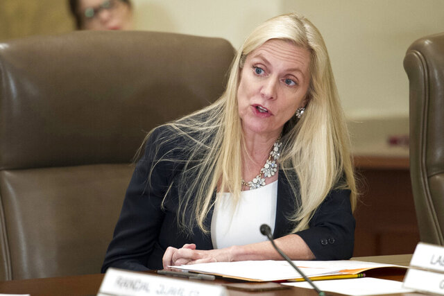 FILE- In this June 14, 2018, file photo Federal Reserve Board Governor Lael Brainard participates in an open meeting in Washington.  Brainard warned Tuesday, July 14, 2020,  that the U.S. economy appears to be slowing after an initial burst of recovery and called for the Fed to take aggressive steps to spur growth.  (AP Photo/Cliff Owen, File)