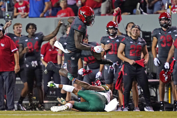 North Carolina State running back Ricky Person Jr. (8) jumps over South Florida safety Matthew Hill during the first half of an NCAA college football game in Raleigh, N.C., Thursday, Sept. 2, 2021. (AP Photo/Gerry Broome)