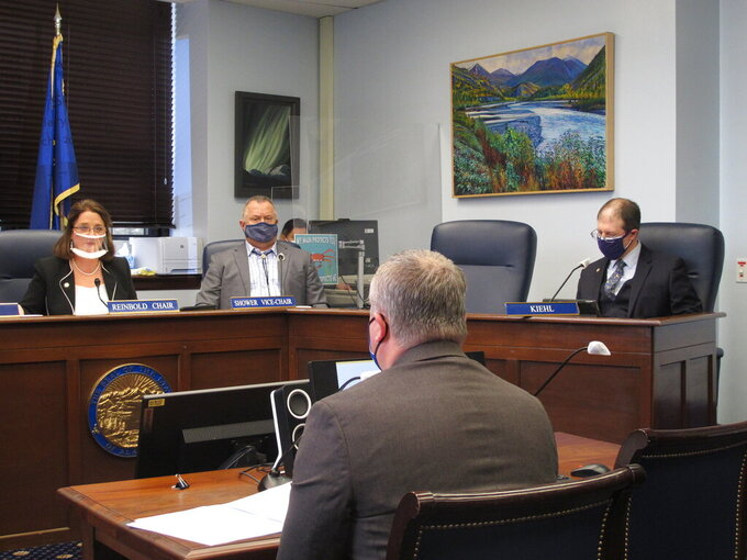State Sen. Lora Reinbold, left, speaks to Attorney General Treg Taylor, foreground, during a confirmation hearing for Taylor on Wednesday, March 24, 2021, in Juneau, Alaska. Also shown are Sen. Mike Shower, second from left, and Sen. Jesse Kiehl. (AP Photo/Becky Bohrer)