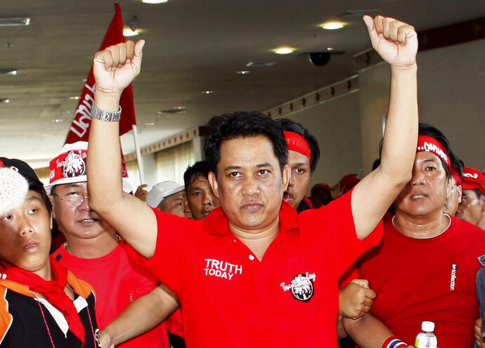 FILE- in this April 11, 2009, file photo, anti-government leader Arisman Pongruangrong is cheered as he and others march through the 14th ASEAN Convention Center in Pattaya, Thailand. Thailand's Supreme Court has affirmed the prison sentences of 12 members of the