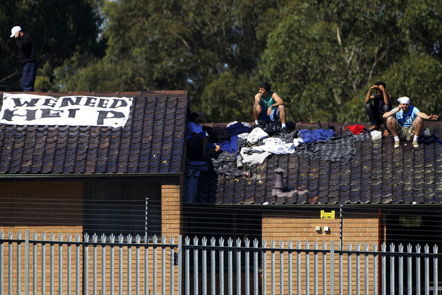 FILE - In this April 12, 2011, file photo, Five male detainees gather on a rooftop of the Villawood Detention Center in Sydney, Australia. The United States is expected to have resettled more than 1,100 refugees by early next year under a deal President Donald Trump reluctantly honored with Australia, an Australian official said on Monday, Oct. 19, 2020. (AP Photo/Rick Rycroft, File)